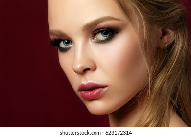 Beauty portrait of young woman with classic make up. Perfect skin and colorful smokey eyes makeup, smokey eyes. Studio shot. Sensuality, passion, trendy luxurious makeup concept.