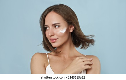 beauty portrait of young woman with cosmetic cream on her face on blue background