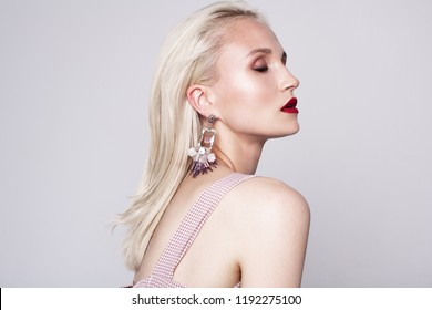 beauty portrait of young woman with earrings, long blonde hair and bright makeup. Red lips. Gray background