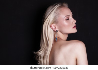 beauty portrait of young woman with earrings, long blonde hair and bright makeup. Red lips. Black background