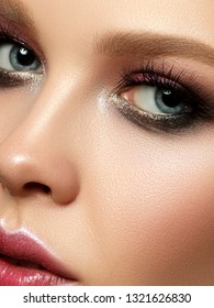 Beauty portrait of young woman with fashion make up. Perfect skin and colorful smokey eyes makeup. Studio shot. Sensuality, passion, trendy luxurious makeup concept. Extreme closeup, partial face view