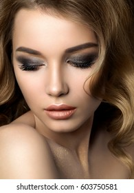 Beauty portrait of young woman with golden makeup. Perfect skin and fashion makeup, smokey eyes. Studio shot. Sensuality, passion, trendy luxurious makeup concept.
