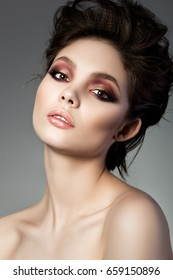 Beauty portrait of young woman with modern smokey eyes makeup. Perfect skin and fashion makeup, smokey eyes. Studio shot. Sensuality, passion, trendy luxurious makeup and cosmetology concept.