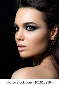Beauty portrait of young woman. Perfect skin and evening makeup. Model posing over black background. Silver smokey eyes. Classic makeup concept. Studio shot.