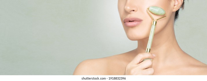 Beauty portrait of a young woman with smooth fresh skin using a jade roller for a facial massage in a panorama banner with close up cropped view of her face and copy space. Facial treatments
