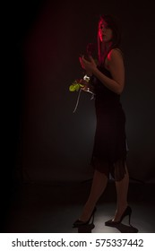 Beauty portrait of young woman standing with a red rose in the hand. Black background with blue backlight