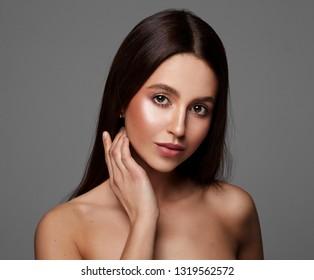 Beauty portrait of young woman touching heek