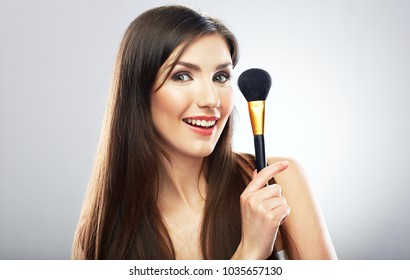 Beauty portrait of young woman using make up brush. Isolated studio portrait.