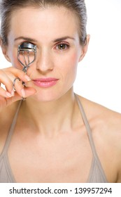 Beauty portrait of young woman using eyelash curler