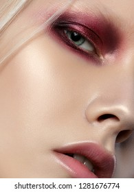 Beauty portrait of young woman with white brows and hair. Perfect skin and fashion makeup. Red smokey eyes. Studio shot. Sensuality, passion, trendy youth makeup concept. Extreme closeup, partial face