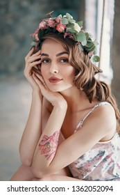 Beauty portrait of young woman with wreath of flowers in her hair