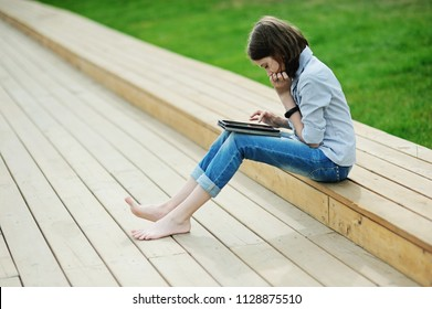 Beauty pre teen kid girl using her tablet pad in the summer park