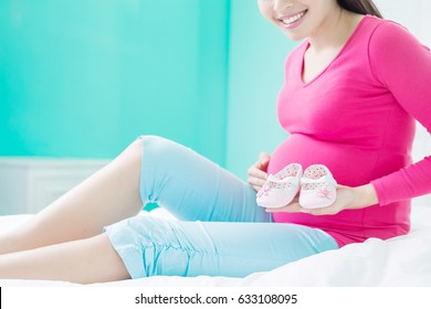 beauty pregnancy woman with baby shoes on the bed