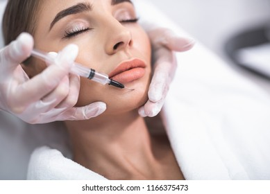 Beauty procedure. Close up portrait of attractive young lady with closed eyes and beautician arms with syringe
