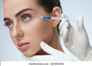 Beauty Procedure. Portrait Beautiful Young Woman Receiving Hyaluronic Acid Injection. Closeup Of Hands In Gloves Holding Syringe Near Attractive Female Face. Facial Beauty Injections. High Resolution