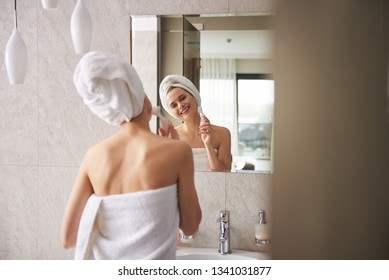 Beauty procedure for skin care. Back side waist up portrait of happy smiling woman wrapping in towel in bathroom cleaning face by dermal brush before mirror