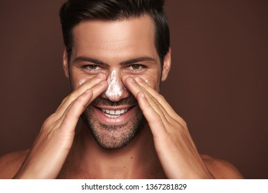 Beauty procedure and skin care. Close up portrait of happy young manful man rubbing face mask on around nose zone. Isolated on brown