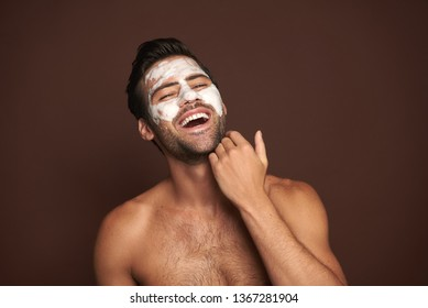 Beauty procedure and skin care. Close up portrait of happy laughing topless man with face mask touching his bristle. Isolated on brown