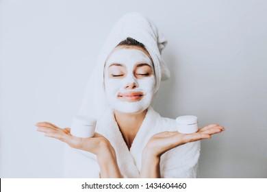 Schönheit behandelt Hautpflegekonzept. Junge Frau, die sich im Badezimmer mit einer Gesichtsgraumatratzmaske aus Lehm im Gesicht aufsetzt.Schöne Frau nach der Dusche mit einem Handtuch auf ihrem Kopf, das sich im Gesicht lächelt.