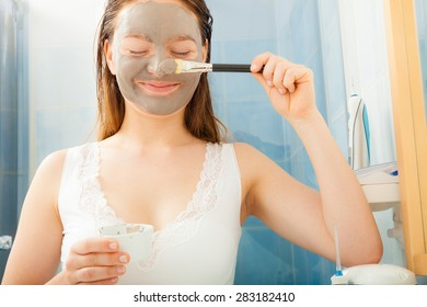Beauty procedures skin care concept. Young woman applying facial gray mud clay mask to her face in bathroom