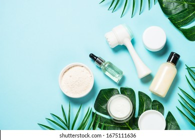Beauty product. Face massage brush, hyaluronic acid, cream for face, clay mask on blue background. Skin care concept. Flat lay image with copy space.