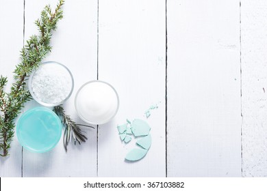 beauty product samples and bath salt with fresh lavender and evergreen leaves on white wood table