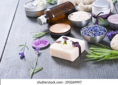beauty product samples with fresh purple and blue dried lavenders, bath salts on dark wood table background