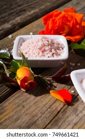beauty product samples with rose flowers and buds on weathered old wooden table