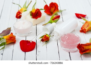 beauty product samples with roses on white wooden, soft light