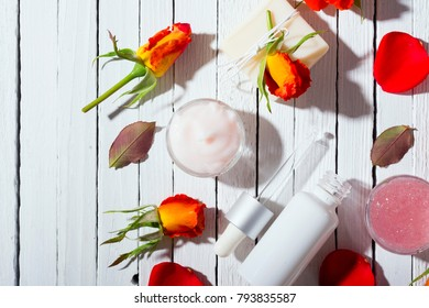 beauty product samples and roses with shade on white wooden table