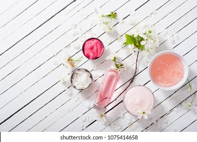 beauty products and cherry blossom on white wood table