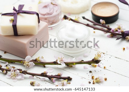 beauty products collection with peach flowers on white wooden