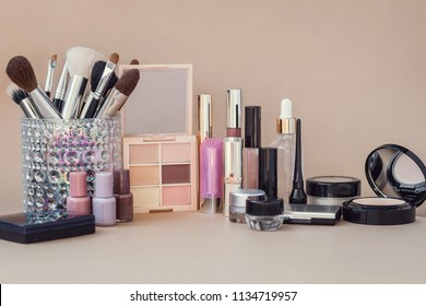 Beauty products on a beige background. Make-up brushes, concealer, foundation, lipsticks, nail polish, mascara.