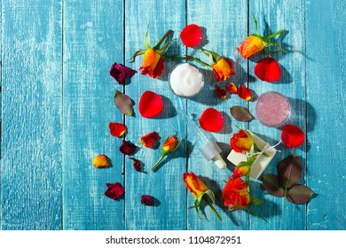 beauty products with rose flowers and petals on blue wooden table background