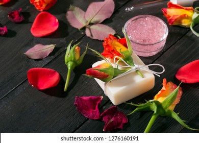 beauty products with roses on black wooden