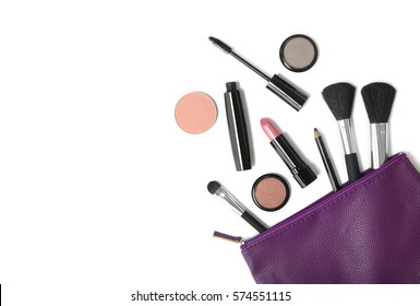 Beauty products spilling out of a purple leather make up bag, isolated on a white background with blank space at side