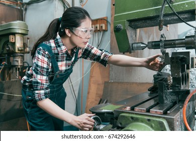 beauty professional factory female employee wearing goggles protect eyes and using industrial machine to milling components.