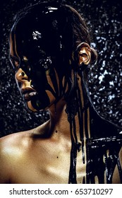 Beauty provocation. Body painting project. Portrait of a young woman with golden skin and black oil pouring on her. Fashionable provocation. Pollution and poisoning concept.
