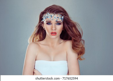 Beauty Queen bride woman with bright blue crystals jewelry on head looking at you camera purple bridal makeup isolated light gray white background wall