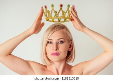 Beauty queen woman blonde put on placing tiara crown on head high self esteem selfishness studio white background