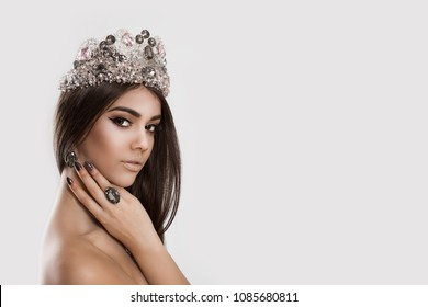 Beauty queen. Woman with crown on head serious facial expression looking at you camera holding hand on her neck isolated white background. Multicultural ethnic model mixed race indian african american