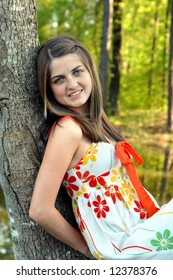 Beauty with a ready smile leans against a tree trunk.  Woods and lake are lit by afternoon sunlight in background.