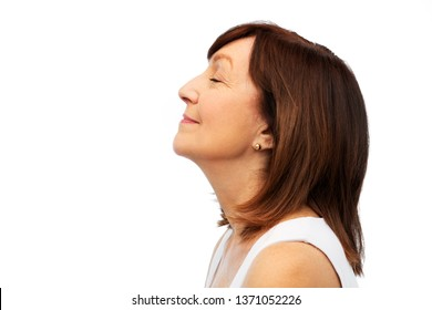 beauty, rhinoplasty and old people concept - profile of smiling senior woman over white background