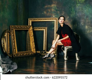 beauty rich brunette woman in luxury interior near empty frames, wearing fashion clothes, lifestyle pretty real people concept