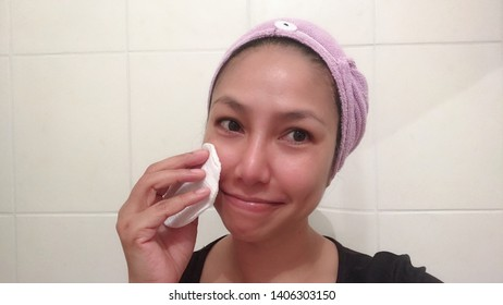 Beauty rituals and makeup techniques; Thai asian woman is removing her makeup