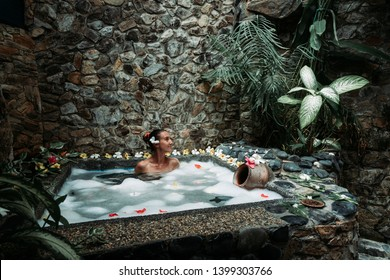 Beauty Rituals in Stunning Environments. Young Woman Taking Bath Full of Flower in Spa in Bali. Tropical Wellness.