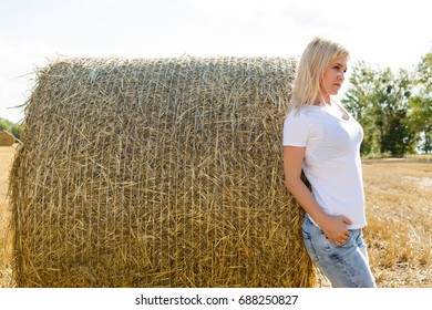 Beauty romantic blonde girl outdoors against hay stack