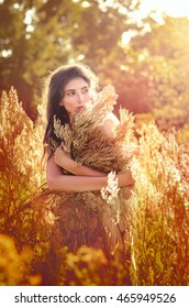 Beauty Romantic Girl, Model Outdoors Dressed in Casual Short Dress on the Field in Sun Light. Blowing Long Hair. Autumn. Glow Sun, Sunshine. Backlit. Toned in warm colors.