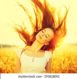 Beauty Romantic Girl Outdoors. Beautiful Teenage Model girl Dressed in Casual Short Dress on the Field in Sun Light. Blowing Long Hair. Autumn. Glow Sun, Sunshine. Backlit