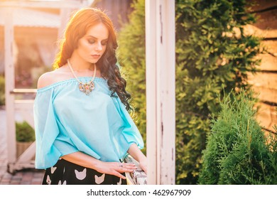 Beauty romantic girl outdoors. Beautiful model young woman with long hair on a nature. Girl with multicolored ling hair and emerald dress. Advertising picture.